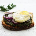 Geröstetes Brot mit Petersilienpesto, Zwiebeln und im Ofen gebackenem Spiegelei