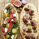 Zwei wunderbare griechische Pizzen mit Rucola, Tomaten, Champignons, grünen Oliven, Kalamata Oliven, Oliven- und Tomatenpaste