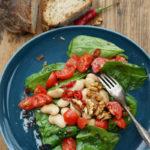 Spinatsalat mit weißen Riesenbohnen, Kirschtomaten, Walnüssen und  einer Himbeermarmelade-Peperoni-Vinaigrette