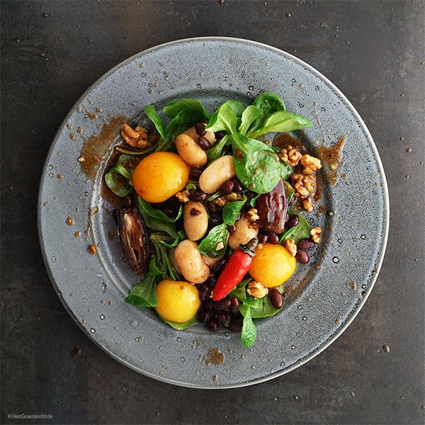 Schwarze Bohnen und weiße Riesenbohnen auf Feldsalat mit Datteln, Aprikosen und einer Pflaumenmus-Walnuss-Vinaigrette