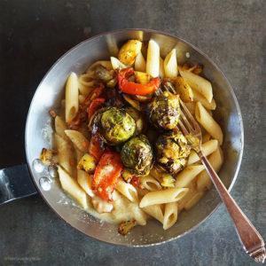 Im Ofen geschmorter spicy Rosenkohl, Paprika, Lauch und Zwiebeln auf Penne Rigate mit einer Erdnuss-Kokosmilch-Sauce