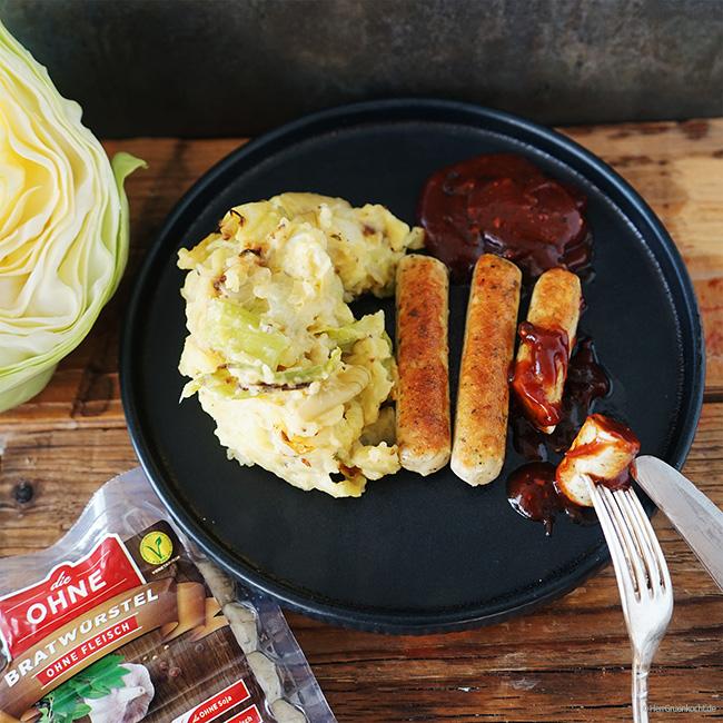 Kartoffelstampf mit geschmortem Spitzkohl und vegetarischen Bratwürstchen