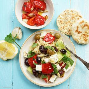 Griechischer Nudelsalat mit Kritharaki, geschmorter Paprika, Tomaten, Gurke, Feta, Oliven, frischer Minze und Sesam-Fladenbrot