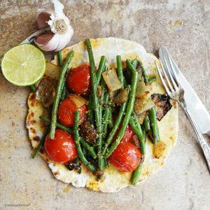 Kichererbsen-Kreuzkümmelfladen mit spicy geschmorten Zwiebeln, Knoblauch, Tomaten, grünen Bohnen und einem Hauch geriebener Limettenschale