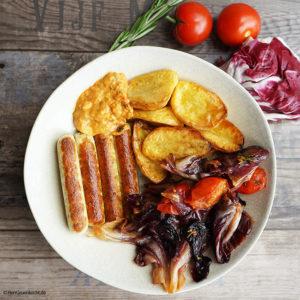 Geschmorter Radicchio, mit Tomaten, roten Zwiebeln, Backofenkartoffeln und vegetarischen Bratwürstchen